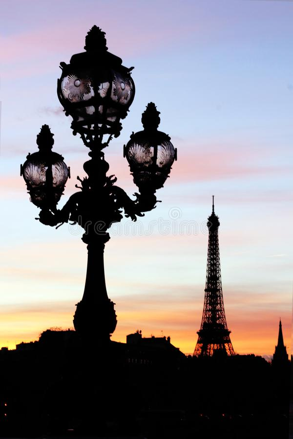 Eiffel tower and Pont Alexandre III bridge lamp posts silhouettes during a Parisian sunset. The Alexandre III bridge and its famous lamp posts builds for the stock photos