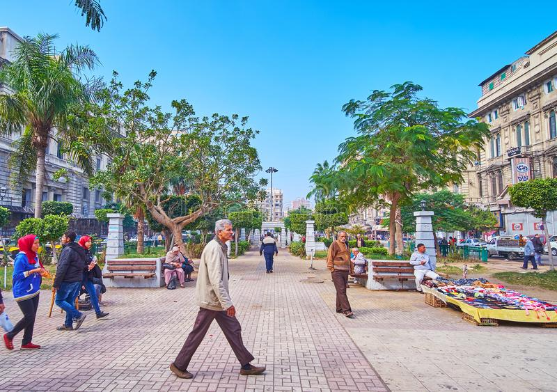 Park in Tahrir square of Alexandria, Egypt. ALEXANDRIA, EGYPT - DECEMBER 17, 2017: The green park occupies the crowded El-Tahrir square, here are always many stock images