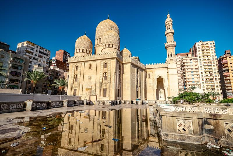 18/11/2018 Alexandria, Egypt, Incredibly beautiful mosque Abo El Abass on the background of blue sky and palm trees on a sunny day. Is reflected in the puddle stock images