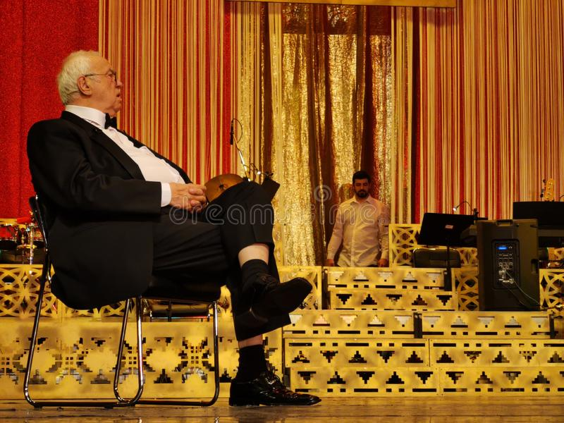 Alexandru Arsinel on the stage of the Theater of the Magazine Constantin Tanase. Alexandru Arsinel sitting on a chair on the stage of the Theater Constantin stock image