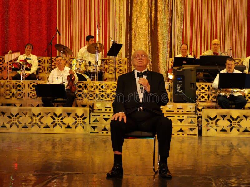 Alexandru Arsinel-zitting op een stoel en het zingen op het stadium van het Theater Constantin Tanase royalty-vrije stock foto