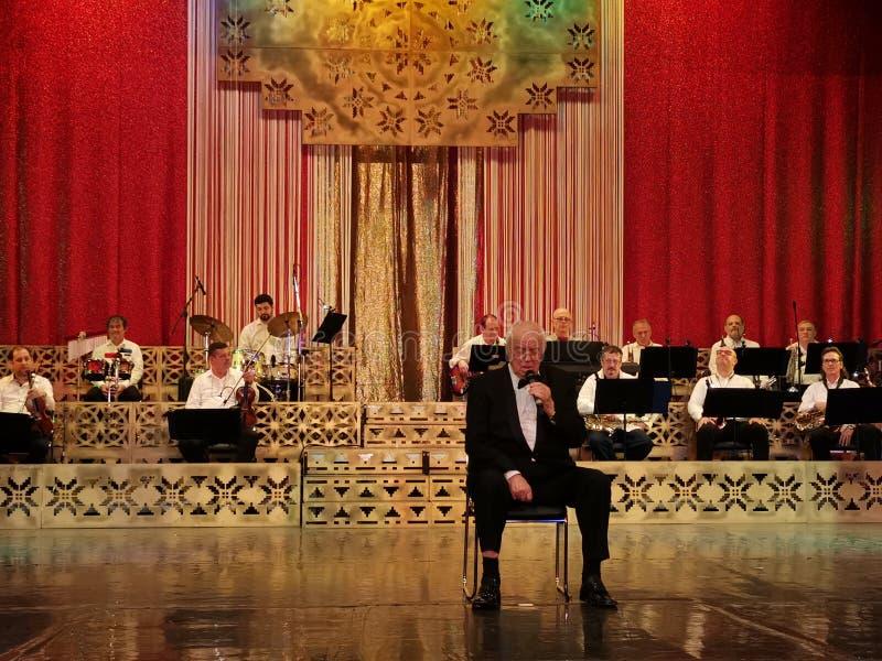Alexandru Arsinel-zitting op een stoel op het stadium van het Theater Constantin Tanase stock afbeeldingen