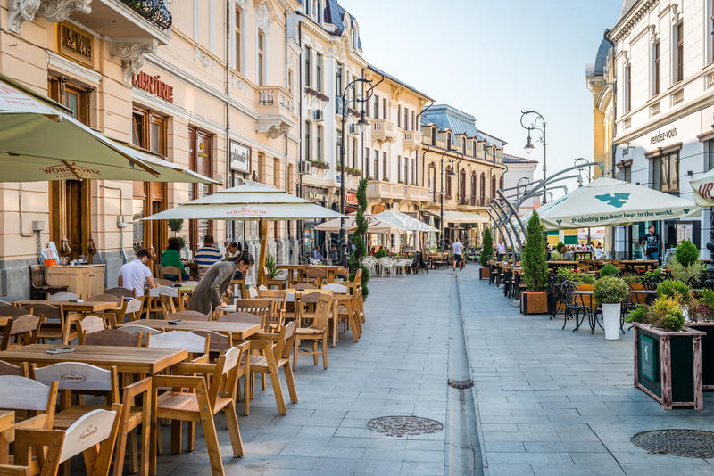 Alexandru Ioan Cuza street in Craiova, Romania. Craiova, Romania - September 16, 2016: People are sitting in cafes on Alexandru Ioan Cuza street in Craiova stock images