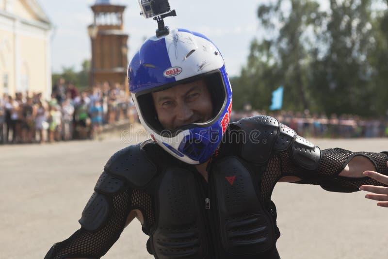 Alexei Kalinin fängt Motorradzeigung im Dorf Verkhovazhye an und begrüßt das Publikum durch die Hand, die in Kreise fährt stockfotografie