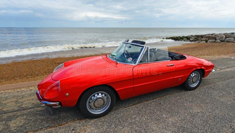 Alfa roja clásica Romeo Sports Convertible Car parqueado en la 'promenade' de la orilla del mar fotos de archivo libres de regalías
