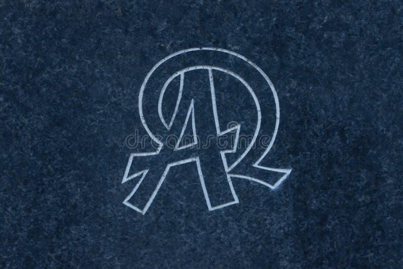 Alfa y Omega talló en la superficie de piedra imagen de archivo