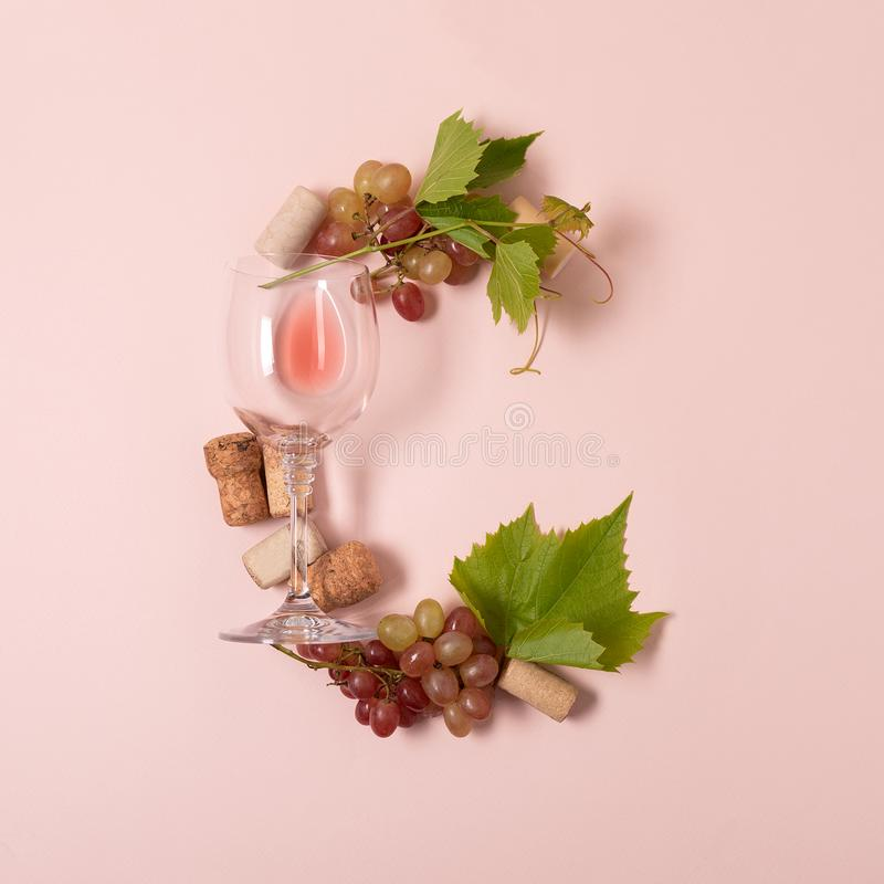 Alfabet Brief C van wijnglazen met roos en witte wijn, druiven wordt de gemaakt, verlaat en kurkt het liggen op roze achtergrond  stock afbeeldingen