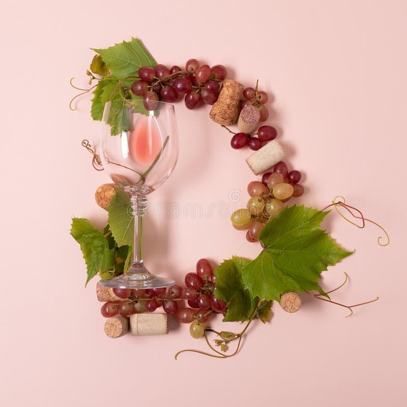 Alfabet Brief D die van wijnglazen met roos en witte wijn, druiven wordt de gemaakt, verlaat en kurkt het liggen op roze achtergr stock afbeelding