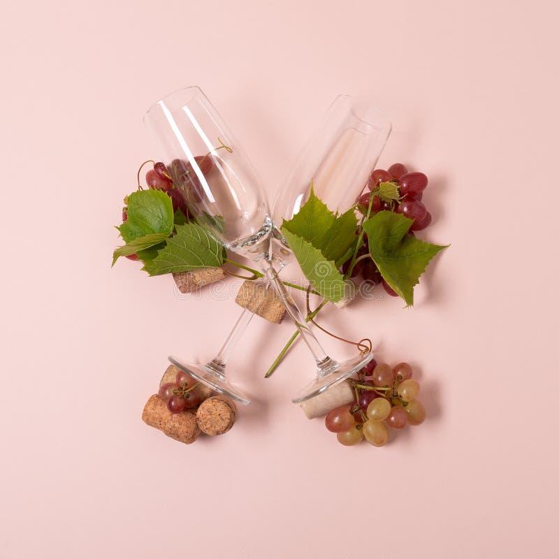 Alfabet Brief X die van wijnglazen met roos en witte wijn, druiven wordt gemaakt, verlaat en kurkt het liggen op roze achtergrond royalty-vrije stock fotografie
