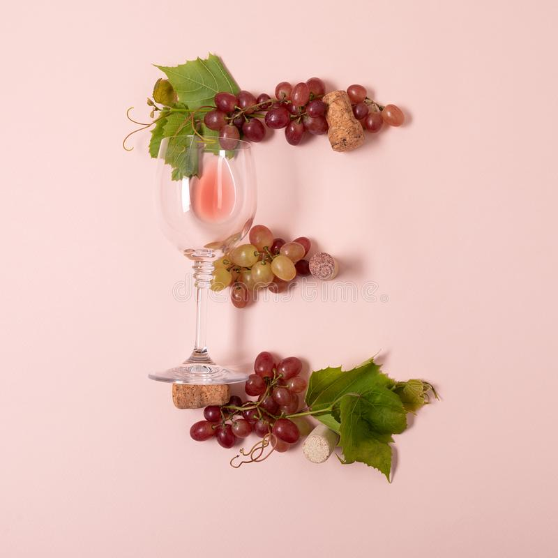 Alfabet Brief E die van wijnglazen met roos en witte wijn, druiven wordt de gemaakt, verlaat en kurkt het liggen op roze achtergr stock foto