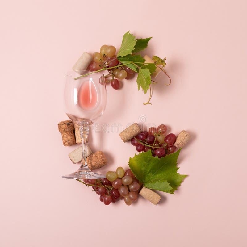 Alfabet Brief G van wijnglazen met roos en witte wijn, druiven wordt de gemaakt, verlaat en kurkt het liggen op roze achtergrond  stock fotografie