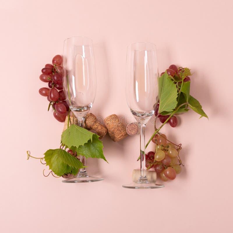 Alfabet Brief H van wijnglazen met roos en witte wijn, druiven wordt de gemaakt, verlaat en kurkt het liggen op roze achtergrond  stock fotografie