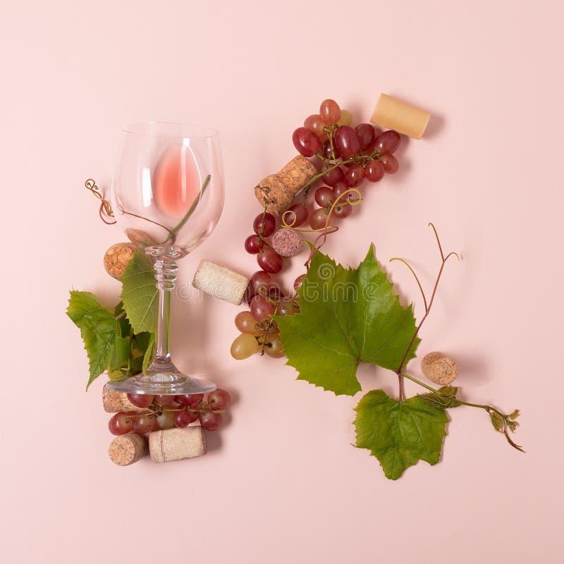 Alfabet Brief K die van wijnglazen met roos en witte wijn, druiven wordt de gemaakt, verlaat en kurkt het liggen op roze achtergr stock foto