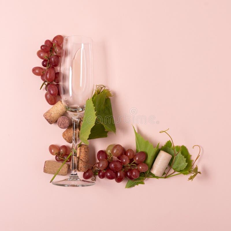 Alfabet Brief L die van wijnglazen met roos en witte wijn, druiven wordt de gemaakt, verlaat en kurkt het liggen op roze achtergr royalty-vrije stock foto