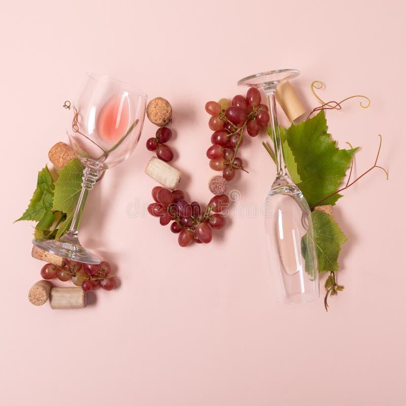 Alfabet Brief M die van wijnglazen met roos en witte wijn, druiven wordt de gemaakt, verlaat en kurkt het liggen op roze achtergr royalty-vrije stock fotografie
