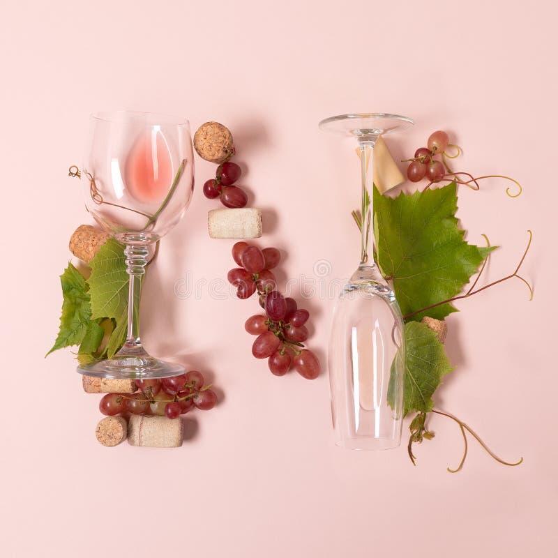 Alfabet Brief N die van wijnglazen met roos en witte wijn, druiven wordt de gemaakt, verlaat en kurkt het liggen op roze achtergr stock foto's