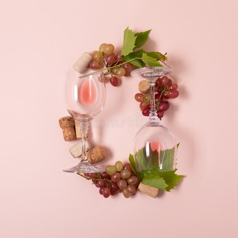 Alfabet Brief O van wijnglazen met roos en witte wijn, druiven wordt de gemaakt, verlaat en kurkt het liggen op roze achtergrond  stock afbeelding
