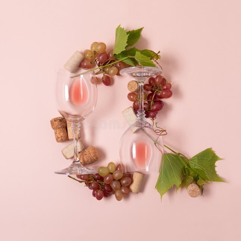 Alfabet Brief Q van wijnglazen met roos en witte wijn, druiven wordt de gemaakt, verlaat en kurkt het liggen op roze achtergrond  royalty-vrije stock foto