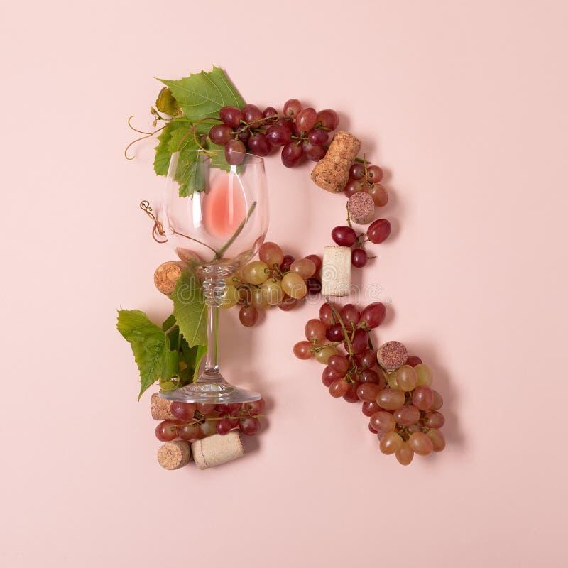 Alfabet Brief R van wijnglazen met roos en witte wijn, druiven wordt de gemaakt, verlaat en kurkt het liggen op roze achtergrond  stock foto