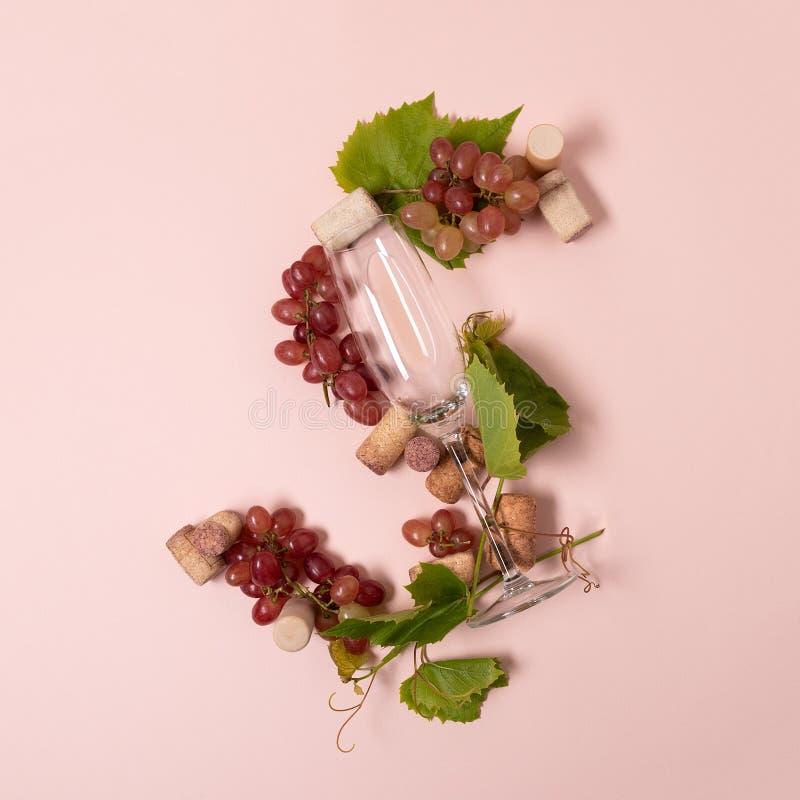 Alfabet Brief S die van wijnglazen met roos en witte wijn, druiven wordt de gemaakt, verlaat en kurkt het liggen op roze achtergr stock foto's