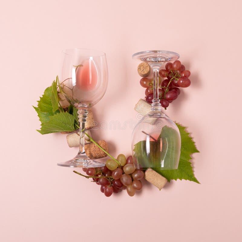 Alfabet Brief U van wijnglazen met roos en witte wijn, druiven wordt de gemaakt, verlaat en kurkt het liggen op roze achtergrond  stock foto's
