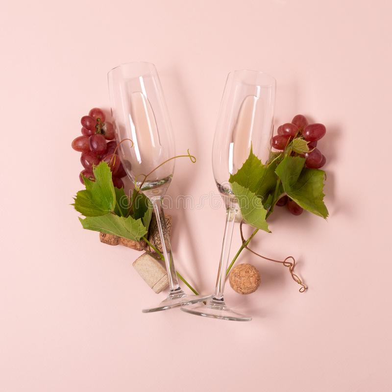Alfabet Brief V van wijnglazen met roos en witte wijn, druiven wordt gemaakt, verlaat en kurkt het liggen op roze achtergrond die stock fotografie