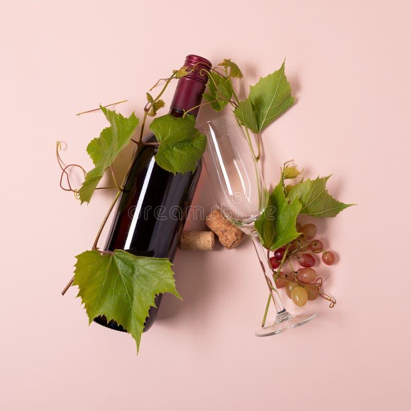 Alfabet Brief A van wijnglazen met roos en witte wijn, druiven wordt de gemaakt, verlaat en kurkt het liggen op roze achtergrond  stock afbeelding