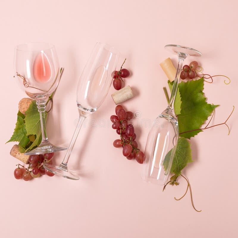 Alfabet Brief W van wijnglazen met roos en witte wijn, druiven wordt de gemaakt, verlaat en kurkt het liggen op roze achtergrond  royalty-vrije stock foto
