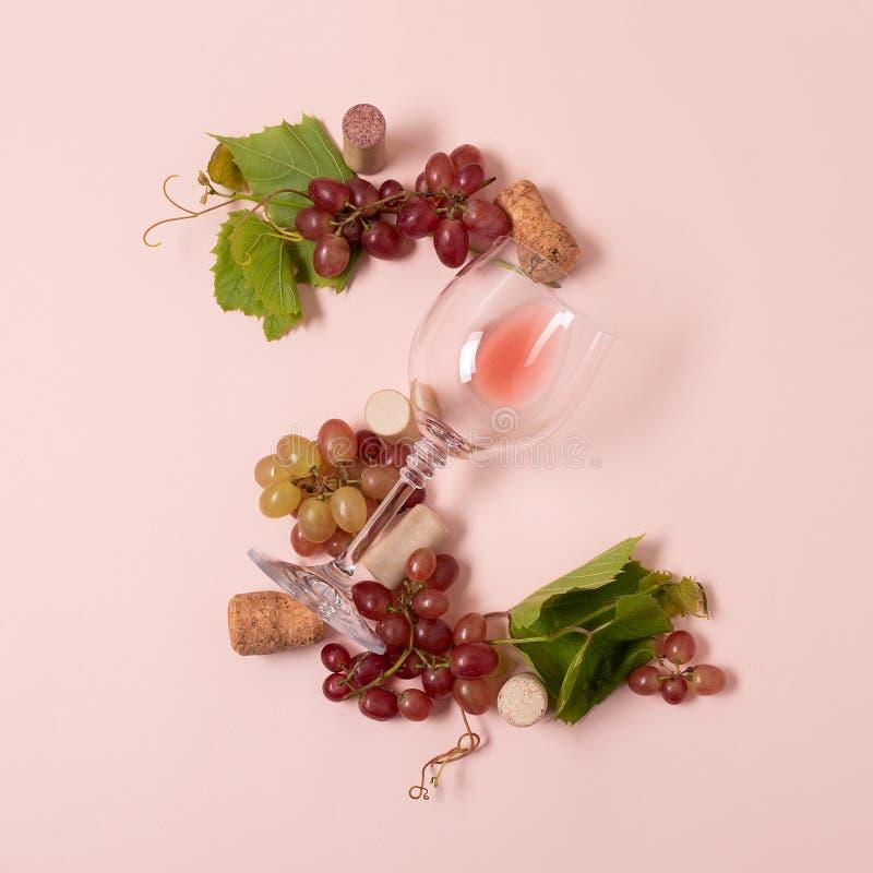 Alfabet Brief Z van wijnglazen met roos en witte wijn, druiven wordt de gemaakt, verlaat en kurkt het liggen op roze achtergrond  stock foto's