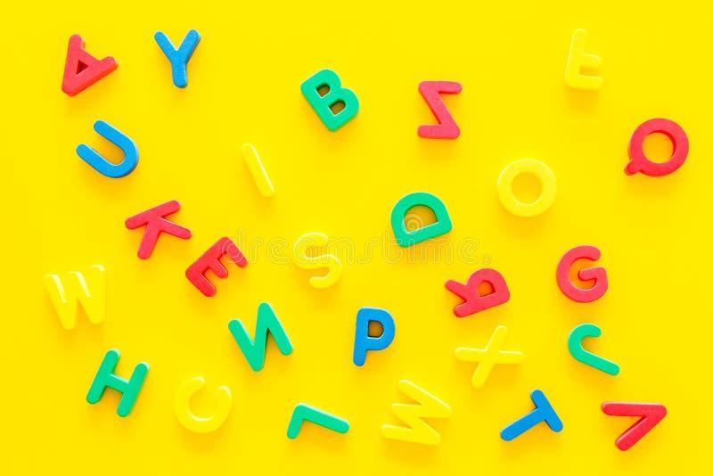 Alfabet för ungebegrepp Engelskabokstäver i oordning på bästa sikt för gul bakgrund arkivbild