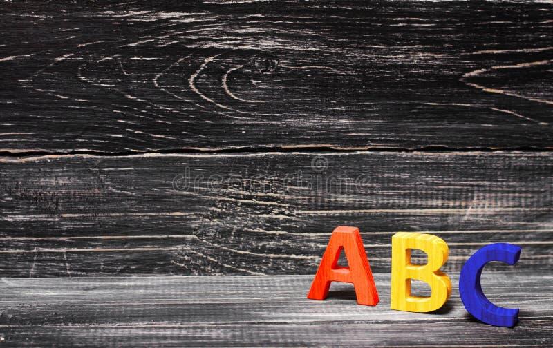 Alfabet som göras av trä på bakgrunden av ett bräde, ebenholts royaltyfria foton
