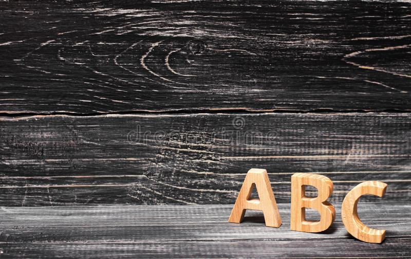 Alfabet som göras av trä på bakgrunden av ett bräde, ebenholts royaltyfri fotografi