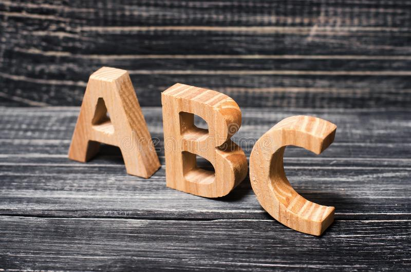 Alfabet som göras av trä på bakgrunden av ett bräde, ebenholts Conce royaltyfri foto