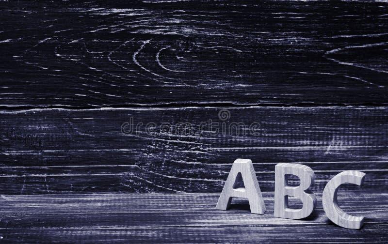 Alfabet som göras av trä på bakgrunden av ett bräde, ebenholts Conce royaltyfria bilder