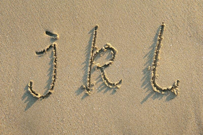 Alfabetbokstäver i sand på strand royaltyfria foton