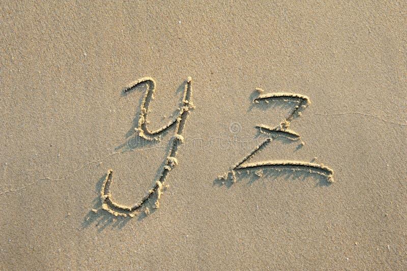 Alfabetbokstäver i sand på strand fotografering för bildbyråer