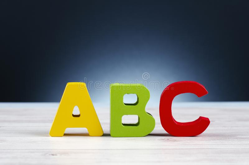 Alfabetbokstavsabc på träskrivbordet över och belysningeffekt royaltyfri fotografi