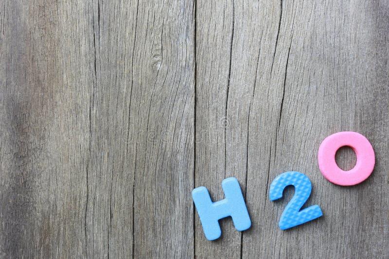 Alfabetet av H2O lägger på gammal brun wood golvbakgrund arkivbilder