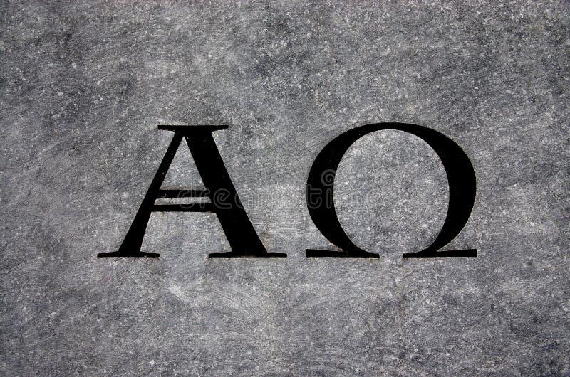 Alfabetisk och omega i sten arkivfoto