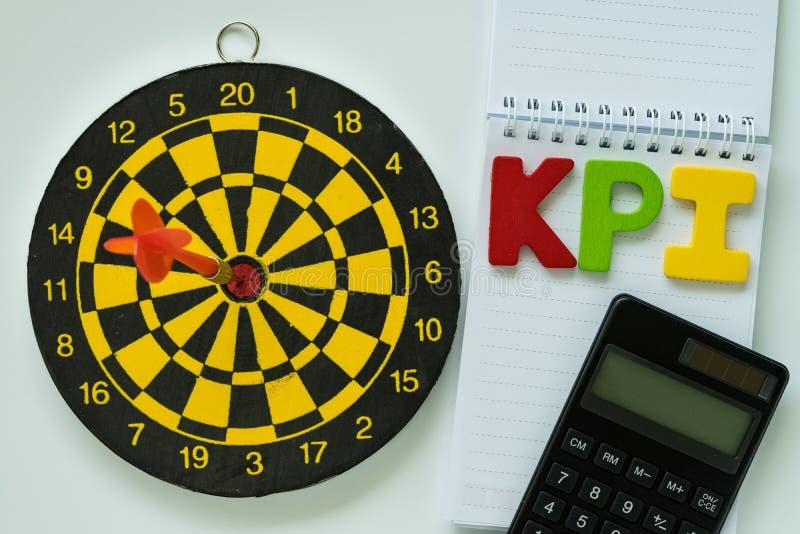Alfabeto de madeira colorido KPI e calculadora na nota do Livro Branco imagem de stock