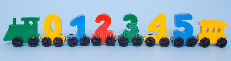 alfabeto di legno dei vagoni delle lettere di numeri 0,1,2,3,4,5 Colori luminosi di verde giallo rosso su un fondo bianco Matemat fotografia stock libera da diritti