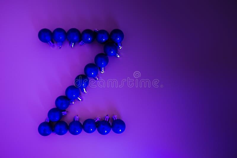 Alfabeto do Natal de bolas de néon azuis do Natal em um fundo do lilás do inclinação imagens de stock royalty free