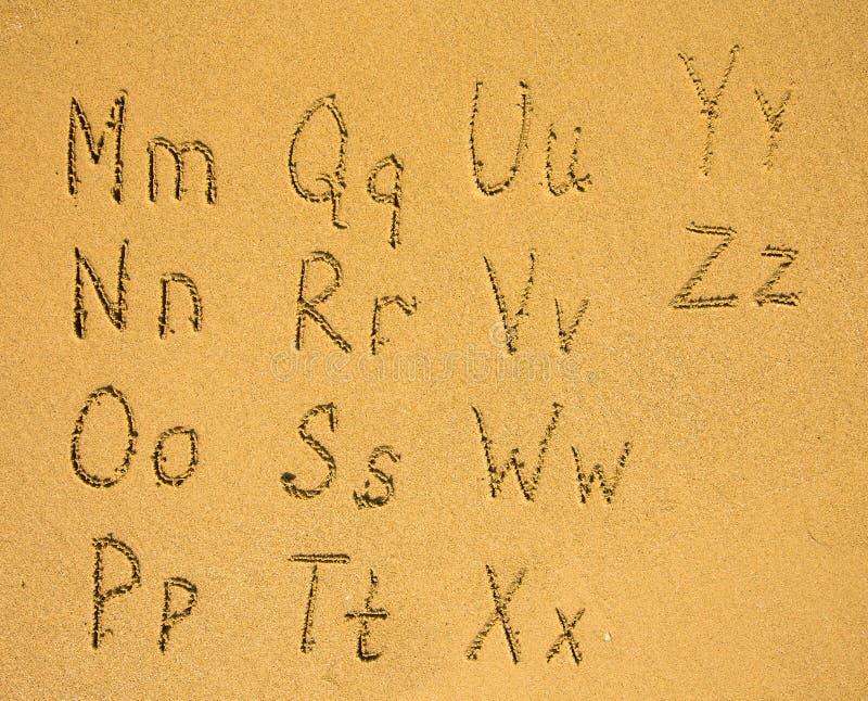 Alfabeto escrito em uma praia da areia fotos de stock
