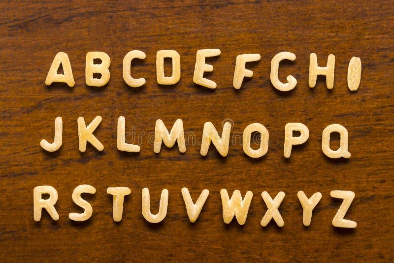 Alfabeto fatto delle lettere dei maccheroni isolate su fondo di legno immagini stock