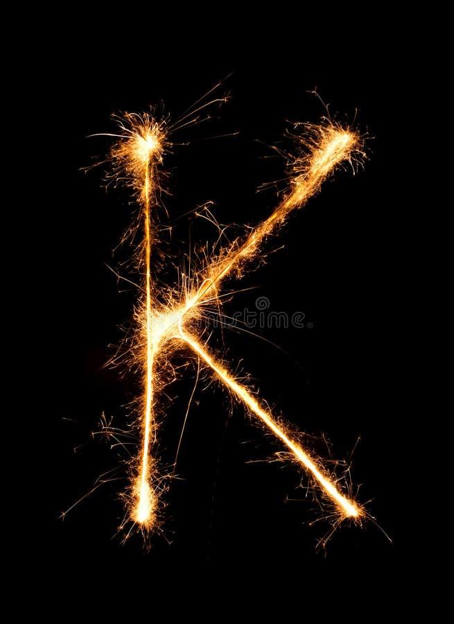 Alfabeto K (mayúsculas) de la luz del fuego artificial de la bengala en la noche imagen de archivo