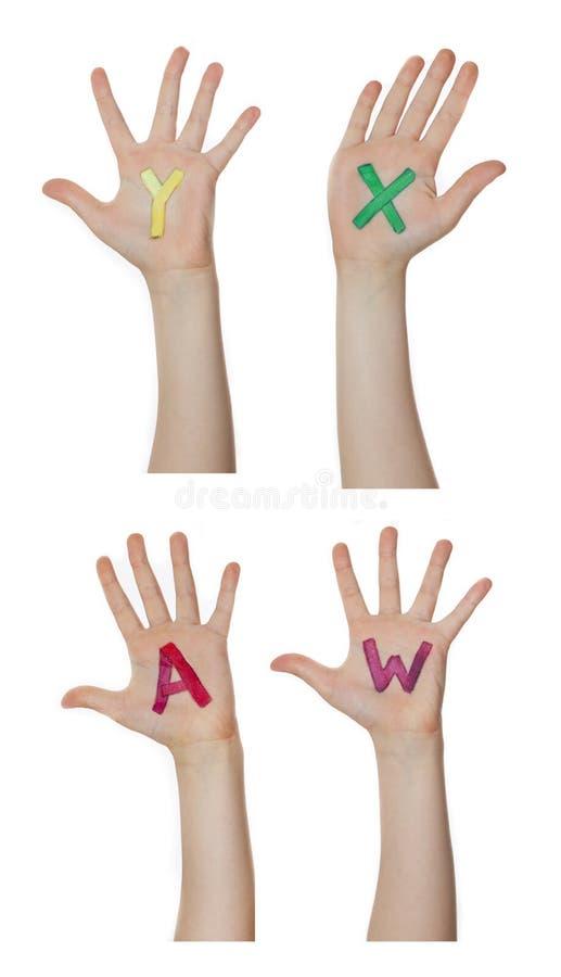 Alfabeto (lettere) dipinto sulle mani dei bambini Aumenta sulle mani fotografia stock libera da diritti