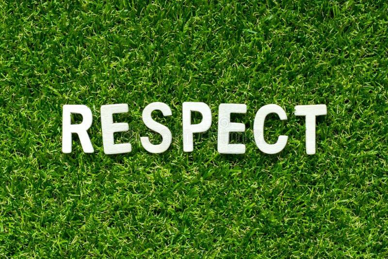 Alfabeto maderero con respeto a la palabra sobre fondo de hierba verde artificial foto de archivo libre de regalías