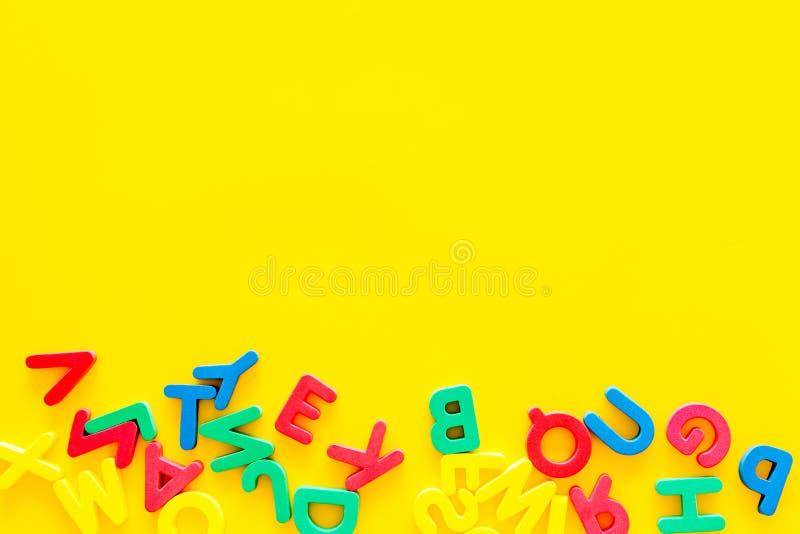 Alfabeto para o conceito das crianças Letras inglesas na desordem no espaço amarelo da cópia da opinião superior do fundo foto de stock