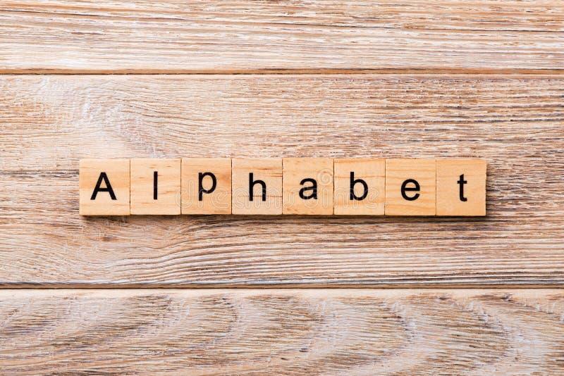Alfabetord som är skriftligt på träsnittet alfabettext på trätabellen för din desing, begrepp fotografering för bildbyråer
