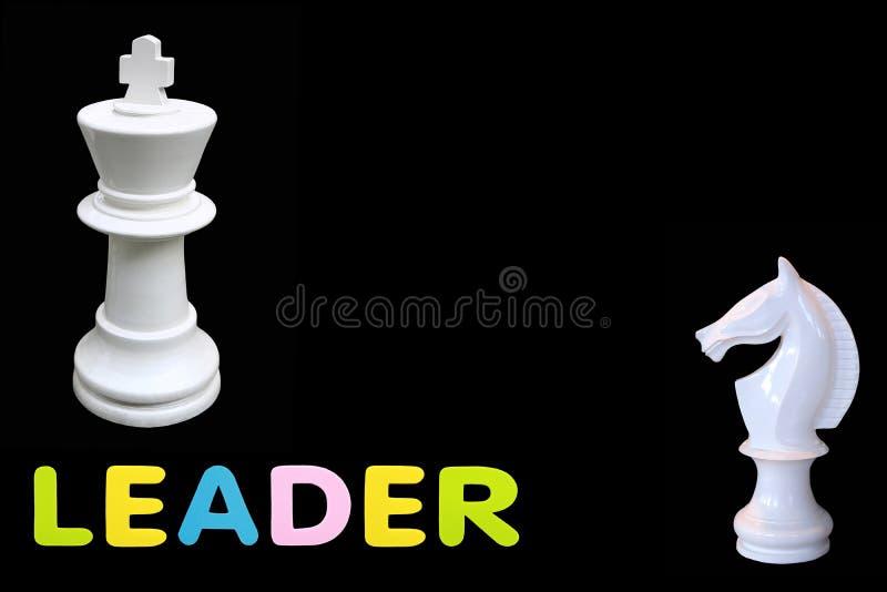 Alfabetsvampgummi av text 'LEDARE 'med schackkonung och hästanseende som isoleras över svart bakgrund Affär och ledare c royaltyfri foto